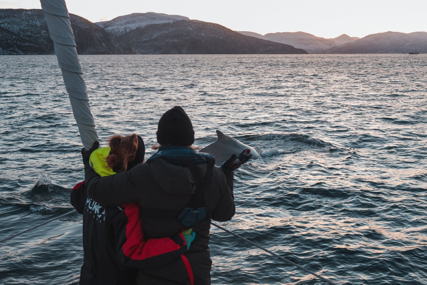 Couple hugging while looking for whales