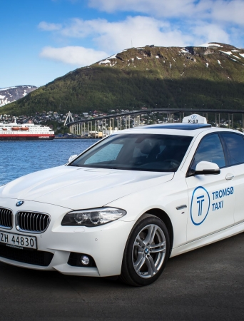 white bmw with the bridge and hurtigruten in the background