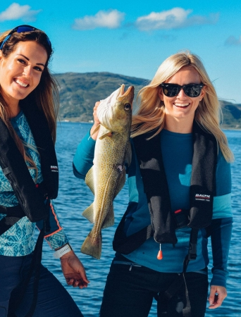 Two women holding a cod each