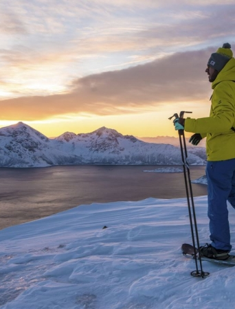 Man on snowshoes enjoying a great view over sea surrounded by snowy mountains