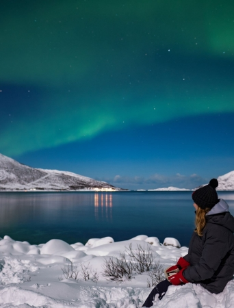 Girl sitting on the snow by the ocean watching the Northern Lights