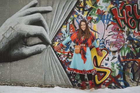 Mariann in her sami dress in front of grafitti
