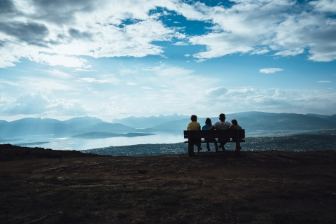 Family sitting on a bench on the top of Mount Storsteinen watching Tromsø city