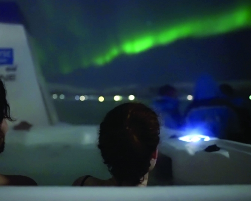 People sitting in jaccuzzi watching the Northern Lights