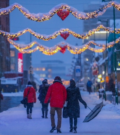 Man and woman walking in the streets of Tromsø during Christmas